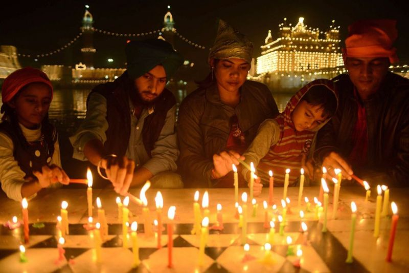 Indian Sikh devotees light candles as they pay their respects at the illuminated Sikhism's holiest shrine Golden Temple in Amritsar on November 12, 2012, on the eve of Bandi Chhor Divas or Diwali. Sikhs celebrate Bandi Chhor Divas or Diwali to mark the return of the Sixth Guru, Guru Hargobind Ji, who was freed from imprisonment and also managed to release 52 political prisoners at the same time from Gwalior fort by Mughal Emperor Jahangir in 1619. (NARINDER NANU - AFP/Getty Images)