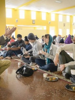 UC Santa Cruz instructor Nirvikar Singh, left, speaks to Hannah Elston, center, Kevin Deutsch, second from right, and Virginia Perez, right, during lunch at the Sikh Gurdwara in San Jose. (David Butow, For The Times / October 21, 2012)