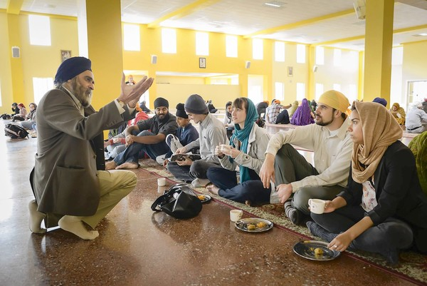 """UC Santa Cruz instructor Nirvikar Singh, left, speaks to Hannah Elston, center, Kevin Deutsch, second from right, and Virginia Perez, right, during lunch at the Sikh Gurdwara in San Jose."" (David Butow, For The Times / October 21, 2012)"