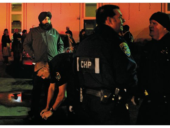 """Karm Bains, left, looks on Saturday night as law enforcement personnel investigate two stabbings following a meeting at a Sikh temple in Yuba City."" (Nate Chute/Appeal-Democrat)"