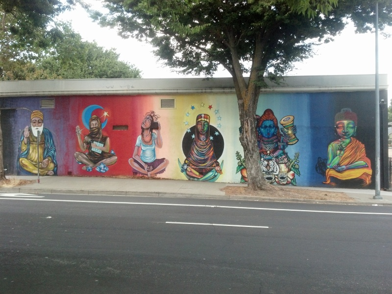 An outdoor mural in Sacramento, California featuring representations of various faiths.