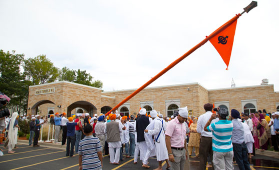 People gather outside the Sikh Temple of Wisconsin for the raising of the Nishan Sahib flag a week after the mass murder that occurred there. A group of about 50 men and boys unwrapped the orange cloth covering the pole, washed the pole with water and milk and then re-wrapped it with a fresh cloth. (source: USA Today)
