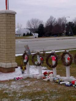 Sign for the Sikh Temple of Wisconsin in Oak Creek, alongside memorials for the six victims of the mass shooting in August. (source: Al Jazeera)
