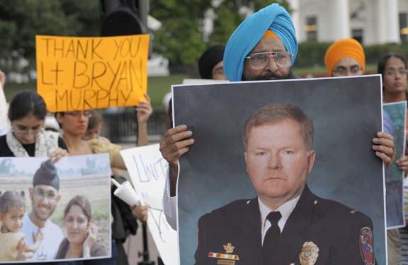 A Sikh man holds a photo of Lt. Brian Murphy during a vigil in front of the White House on August 8, 2012 to commemorate the victims of the Wisconsin Sikh Temple shooting and other victims of hate. (source: Leader-Telegram. Photo credit: AP Photo/Susan Walsh)