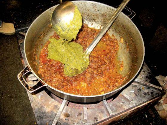 """Chef Partap Singh adds cooked and pureed mustard greens to a sauteed base of garlic, ginger, onion, salt, pepper and chili as he prepares saag, a vegetarian curry, in the kitchen of the Tierra Buena Sikh Temple."" (photo: Laura van der Meer/Appeal-Democrat)"