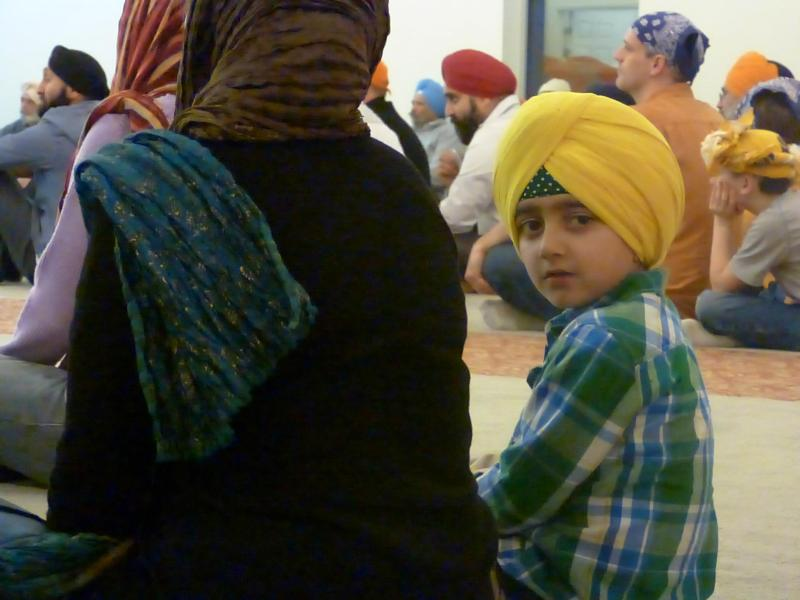 A child takes notice of the camera during the interfaith evening at the Sikh Temple of Utah, March 6 (Photo credit: Andalin Bachman. Source: Salt Lake Interfaith Roundtable Facebook page)