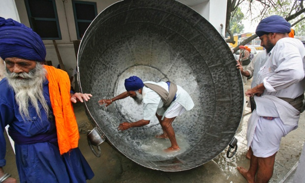 """What is he panning for? A man cleans a huge pan to prepare a non-alcoholic drink during celebrations of Hola Mohalla festival at Anandpur Sahib, India. The Hola Mohalla festival is celebrated during the Hindu religious festival of Holi, marking the congregation of Sikh devotees from all over the country. Photograph: Ajay Verma/Reuters"" (source: The Guardian)"