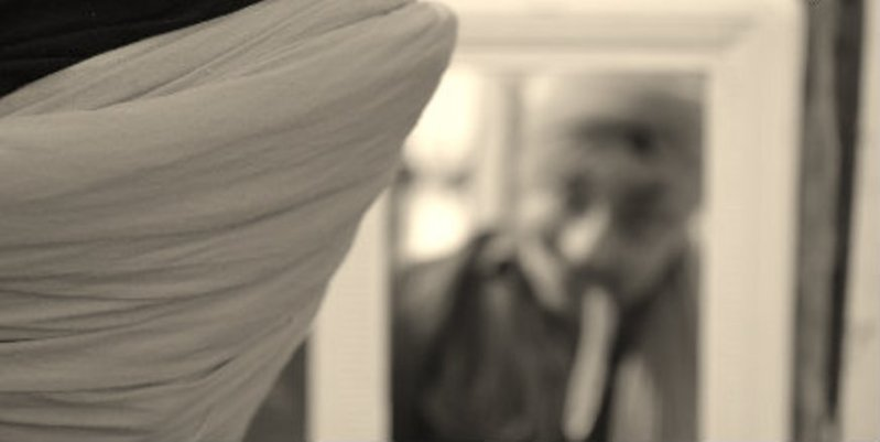 A young Sikh ties his turban in front of a mirror. (adapted photo from Turban King)