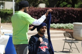 """""""SMU Sikh Students Association President Parminder Deo ties a turban around student Alli Schloeman."""" (source: Christopher Saul / The Daily Campus)"""