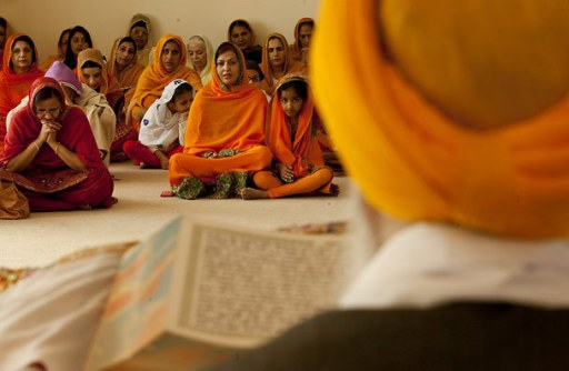 """""""Attendees listen as the Sikh holy book, Sri Guru Granth Sahib, is read. After readings, from 10 a.m. Friday until 10 a.m. Sunday, Gurudwara members prayed, sang worship songs and played the harmonium and tabla."""" (source: Erika Shultz / The Seattle Times)"""