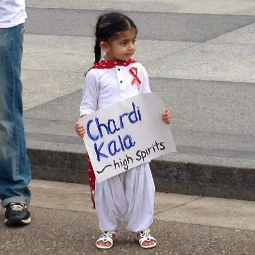 "A young girl holds a sign: ""Chardi Kala - High Spirits"". (source: Just Sikh)"
