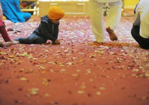 """Ather Singh, 3, plays with some flower petals on the floor of the temple during a celebration of Vaisakhi Gurpurab at the Niskayuna Gurdwara Sahib temple on Sunday, April 14, 2013 in Niskayuna, NY. "" (source: Paul Buckowski / Times Union)"