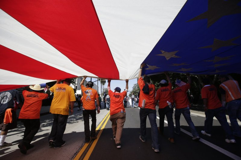 """Union workers march along the street with a huge American flag during a May Day rally in Los Angeles, Wednesday, May 1, 2013. In celebration of May Day, people have gathered across the country to rally for various topics including immigration reform."" (Photo credit: AP Photo 