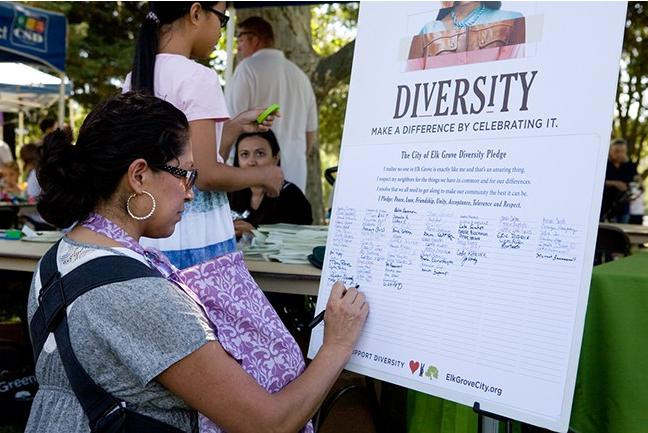 "A participant at the 2012 Elk Grove, California, Multicultural Festival signs a ""Diversity Pledge."" (Source: City of Elk Grove)"
