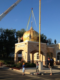 Workers install seven domes now adorn the Sikh Temple of Wisconsin in Oak Creek earlier this month, as tributes to the lives lost in last year's shooting rampage by a white supremacist. (Source: WISN-TV)