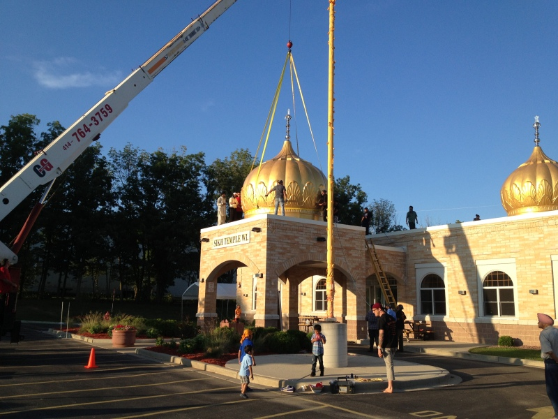 Workers install seven domes at the Sikh Temple of Wisconsin in Oak Creek earlier this month, as tributes to the lives lost in last year's shooting rampage by a white supremacist. (Source:  WISN-TV)