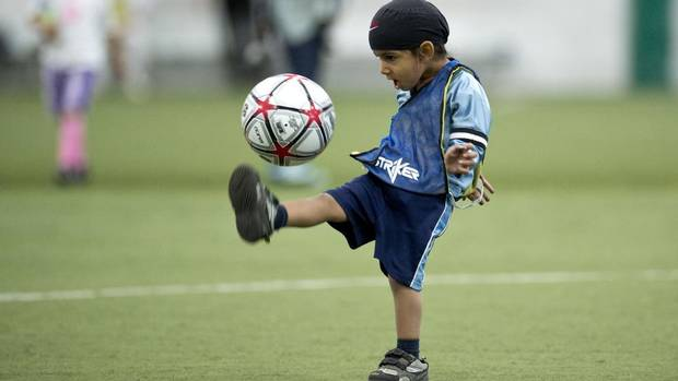 """Harshaan Ahluwalia, 2, dribbles a soccer ball during a friendly soccer match in solidarity with young players who wear turbans Saturday, June 15, 2013 in Montreal. Quebec's soccer federation announced it is ending its much-criticized turban ban Saturday."" (Photo credit: Paul Chiasson 