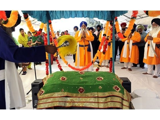 """""""Giani Gurbachan Singh, who traveled from India for the groundbreaking of a new Sikh temple in the 10400 block of Larkin Road in Live Oak, reads from the Sikh holy book, the Guru Granth Sahib, on Friday, Aug. 30, 2013. The 25,000 square foot complex will include three structures on nearly 11 acres and will be the largest Sikh temple site in Yuba-Sutter."""" (Photo: David Bitton/Appeal-Democrat)"""