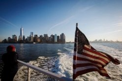"""""""A woman on the deck of a boat headed to Ellis Island in New York."""" (Credit: Lucas Jackson/Reuters. Source: New York Times.)"""