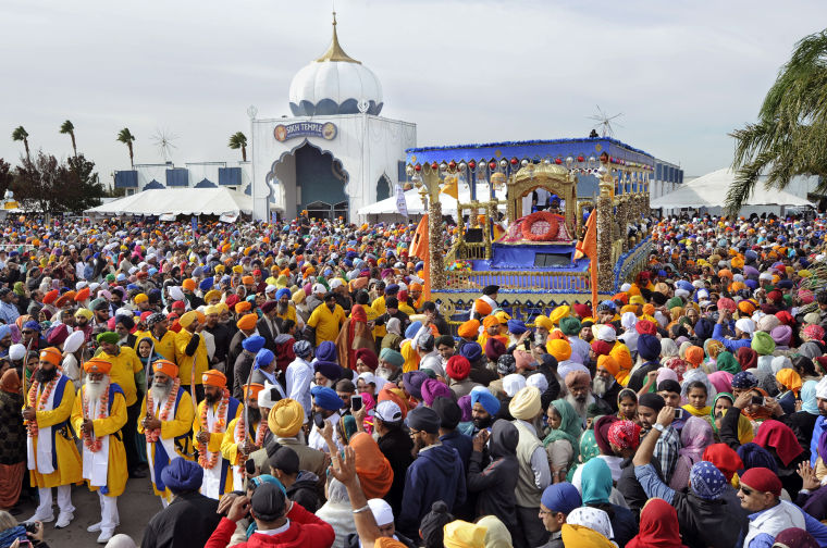 """Thousands of people surround the Guru Granth Sahib, or Sikh holy scriptures, on the main float during the 34th annual Nagar Kirtan and Sikh Parade in Yuba City Sunday, Nov. 3, 2013."" (Photo: David Bitton/Appeal-Democrat)"