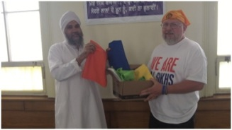 Naresh Singh of the Sikh Gurudwara of Fort Wayne (left) and Carl Jylland-Halverson of the University of Saint Francis pose with school supplies bound for New Delhi (photo by Lori Way).